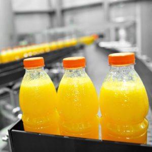 Close-up of orange juice bottles being filled at a bottling facility.