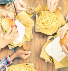 Aerial shot of a group of people eating hamburgers and fries.