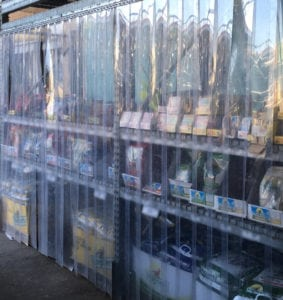 Plastic strip curtain protecting racks of seeds from birds.