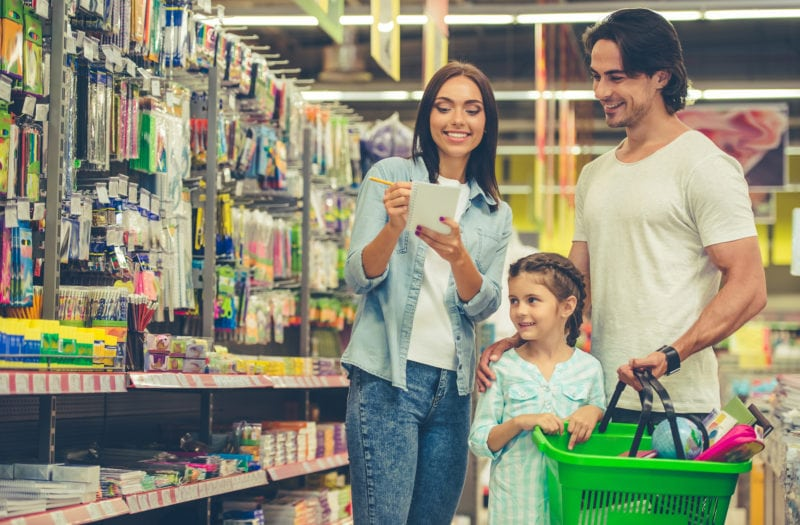Happy, young family shopping at a retail store.