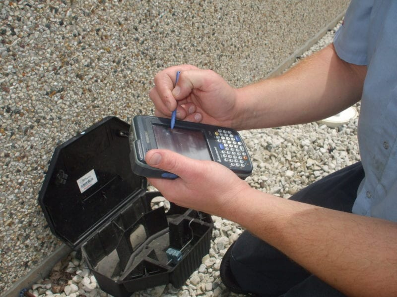 Copesan technician completing documentation on a handheld device.