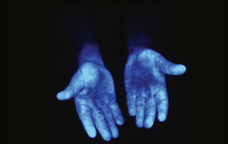 Blue light shining on hands revealing germs.