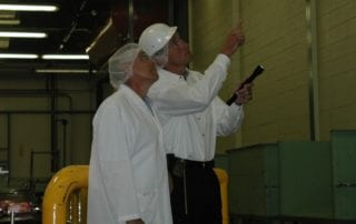 Pest control professional inspecting a warehouse with a client.