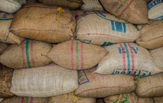 Large stack of burlap coffee bags.