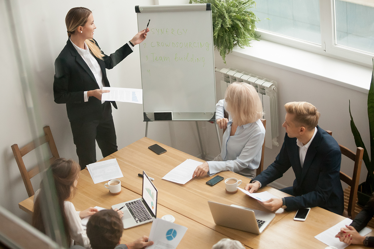 Woman presenting to team in small conference room.
