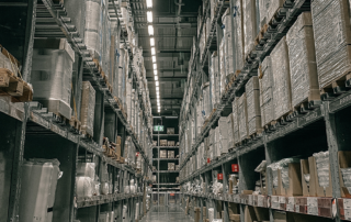 Aisle view in warehouse with boxes on shelves.
