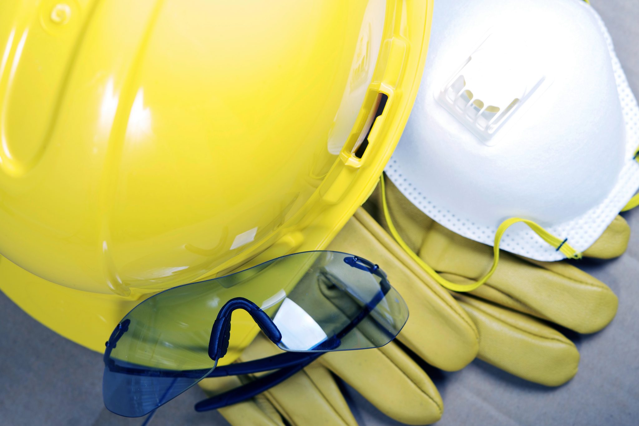 Yellow hard hat, protective glasses, yellow rubber gloves, and PPE mask.