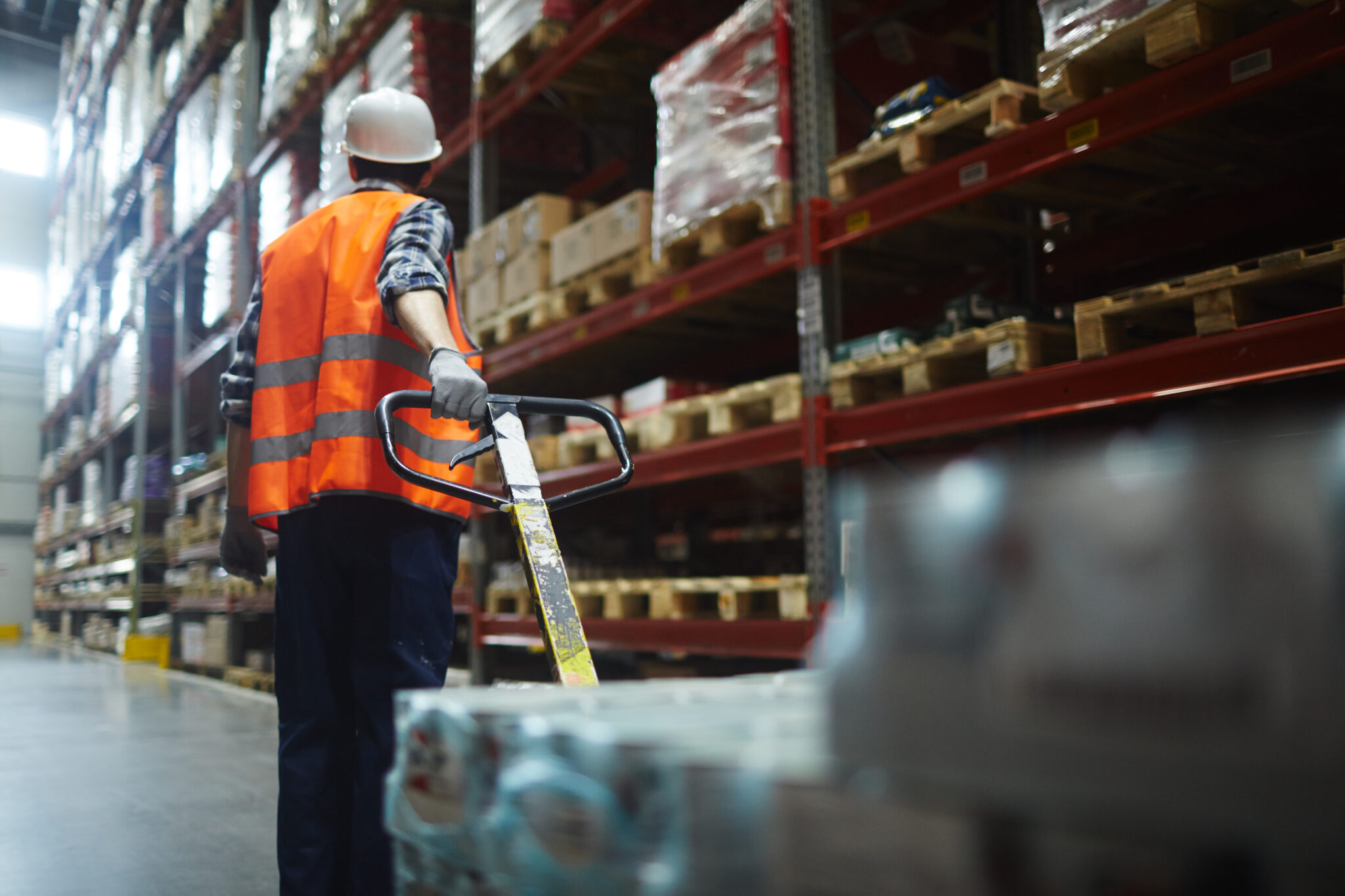 man pulling forklift in warehouse